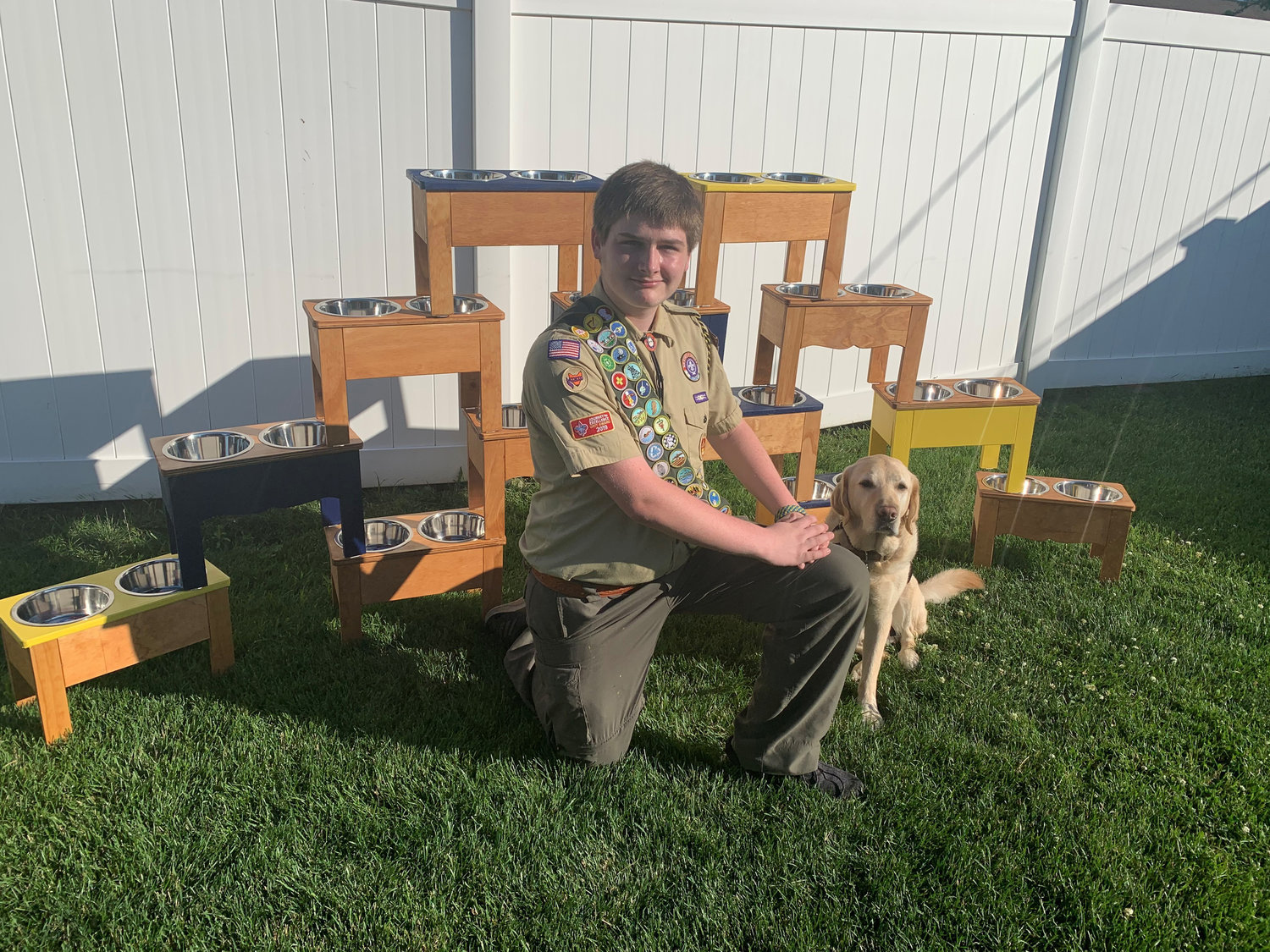 Luke Tordy and Dragon in the back yard of the Tordy home with some of the bowl stands he and his Eagle Scout team made for Canine Companions for Independence at the beginning of the month.