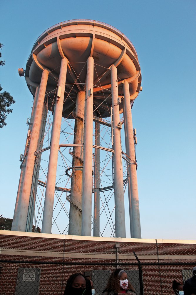 The Elmont water tower has been rusting for years, and blue paint chips are falling off.