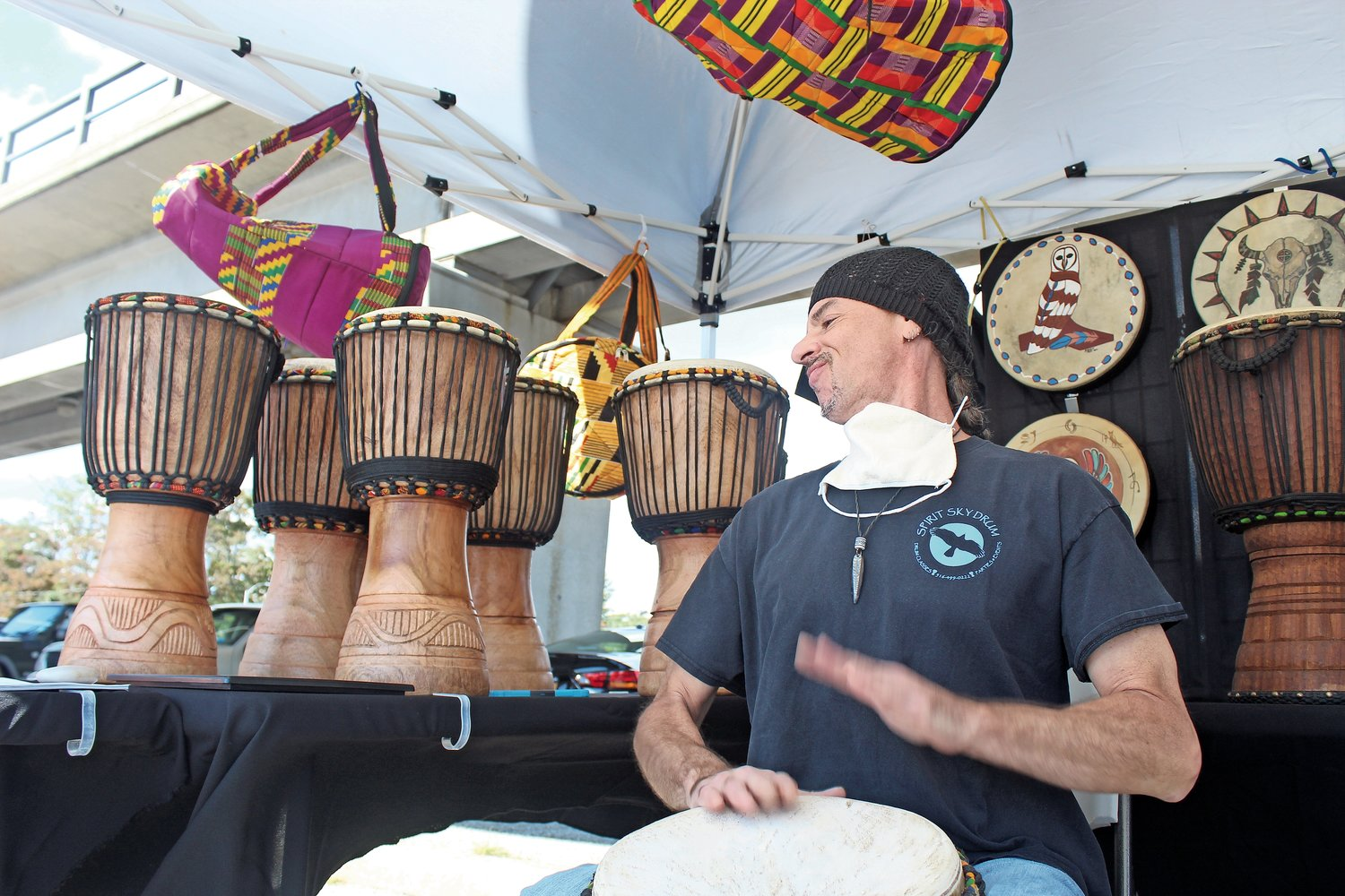 George Schultze, owner of Spirit Sky Drum in Freeport, played a djembe drum to attract visitors to his booth.