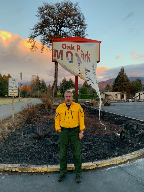 Long Beach lifeguard John Burke in front of a melted motel sign in the City of Gates.