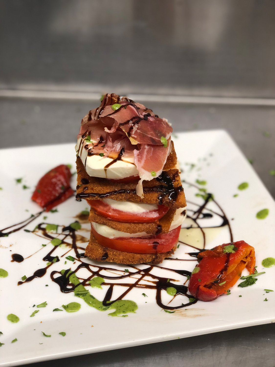 A dish that has garnered Instagram fame is Anthony's Chicken Stack, which features layers of pan-fried cutlets and sliced mozzarella and tomato topped with ribbons of prosciutto and drizzled with pesto and balsamic.