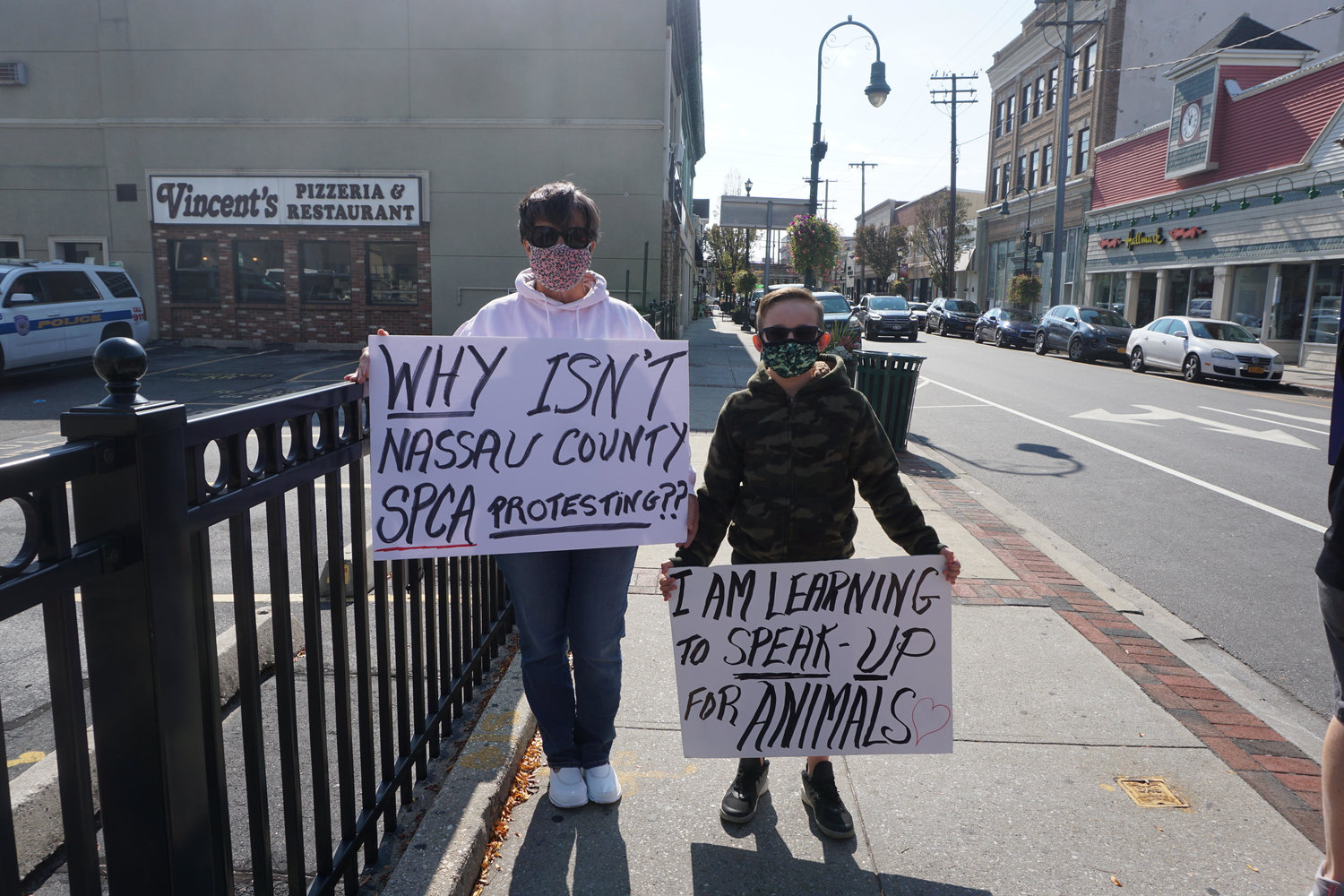 Diane Madden, left, protested outside Shake A Paw with Connor Brugge.
