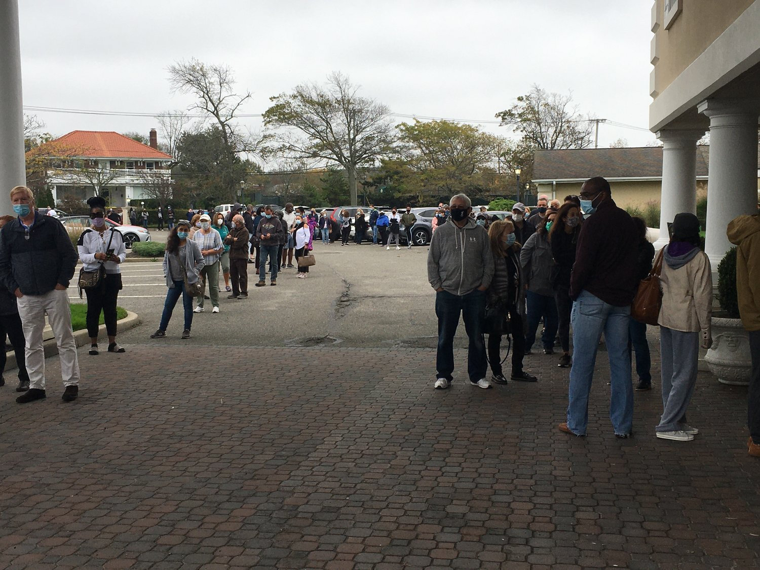 People began waiting outside the Lawrence Yacht and Country Club before the polls opened at 9 a.m. on the first of early voting on Oct. 24.