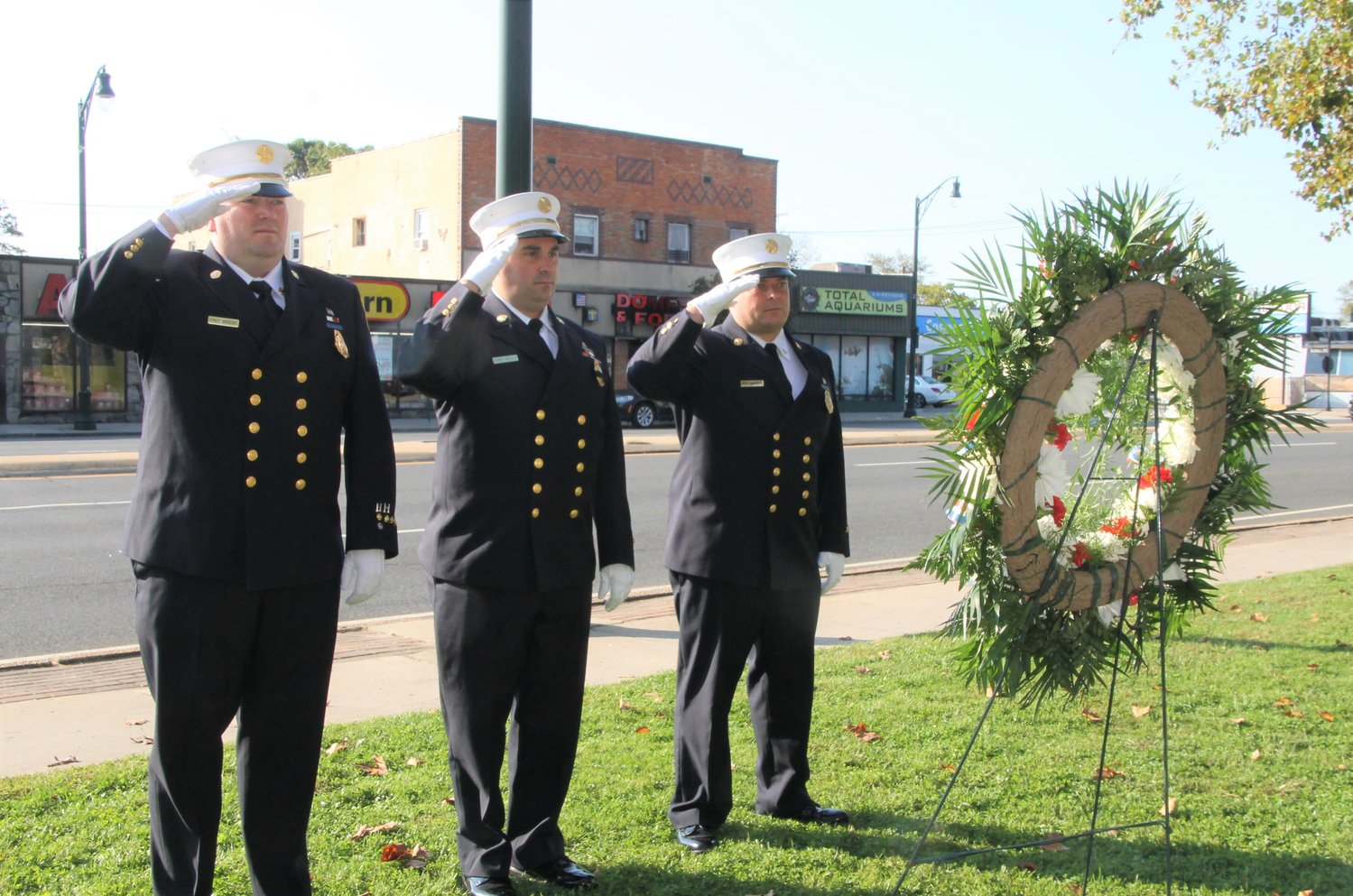 Chief Michael Brooks, far left, Second Assistant Chief Chris Kelly and Third Assistant Chief Danny Ambrosio paid their respects at a stone marker bearing their names and placed a wreath in their memory.