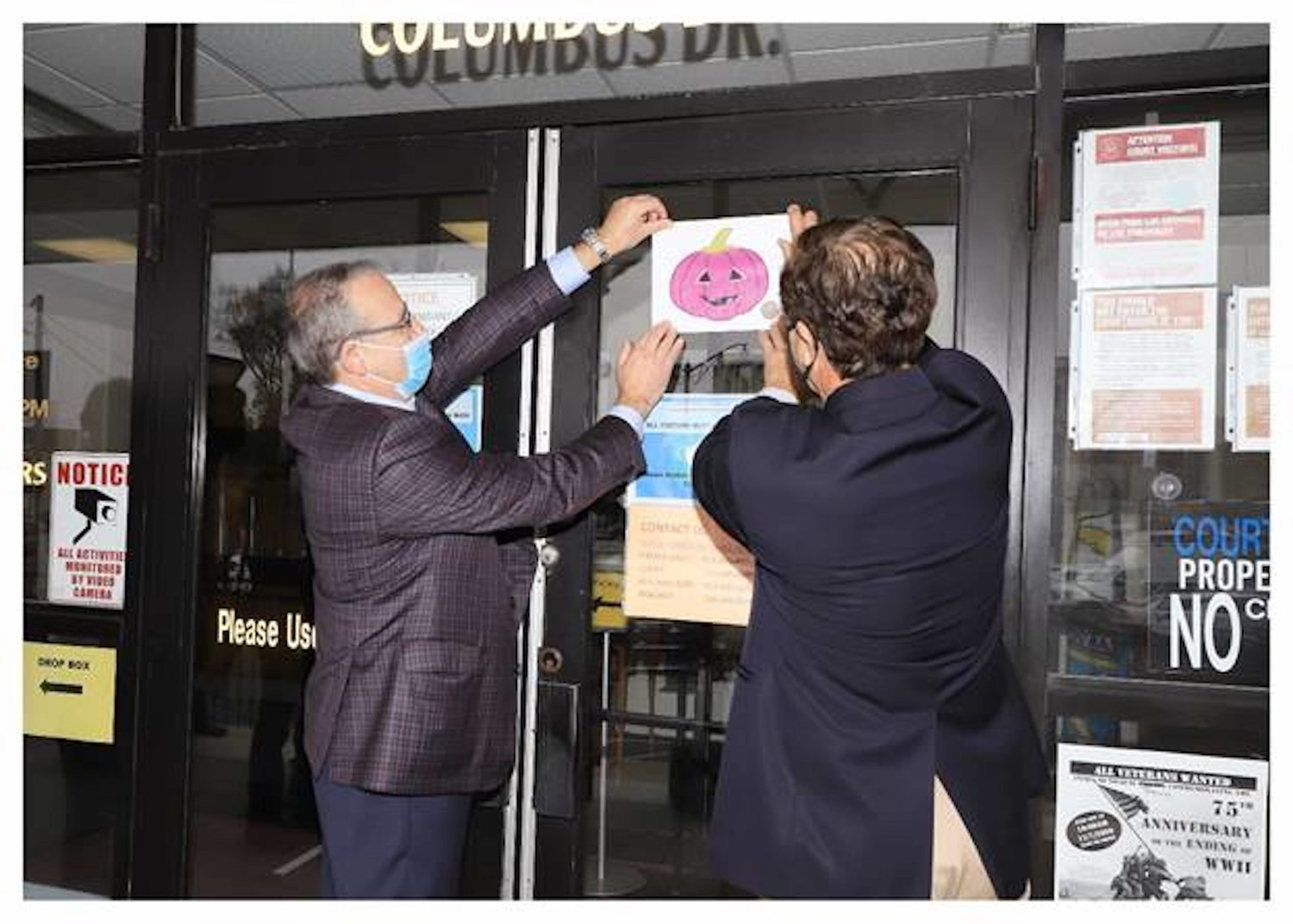 County Legislator William Gaylor, left, and Lynbrook Mayor Alan Beach placed a purple pumpkin on the doors of Village Hall as part of the Purple Pumpkin Halloween Project, which promotes a safe and healthy holiday amid the pandemic.