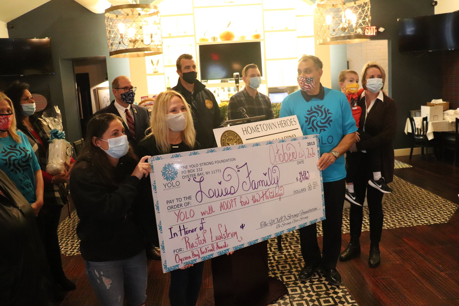 Cheryl Lordi, left, Danielle Taylor, the co-founder of the YOLO Strong Foundation and Town of Oyster Bay Supervisor Joseph Saladino held up a check that will guarantee financial assistance for a local family during the holidays.