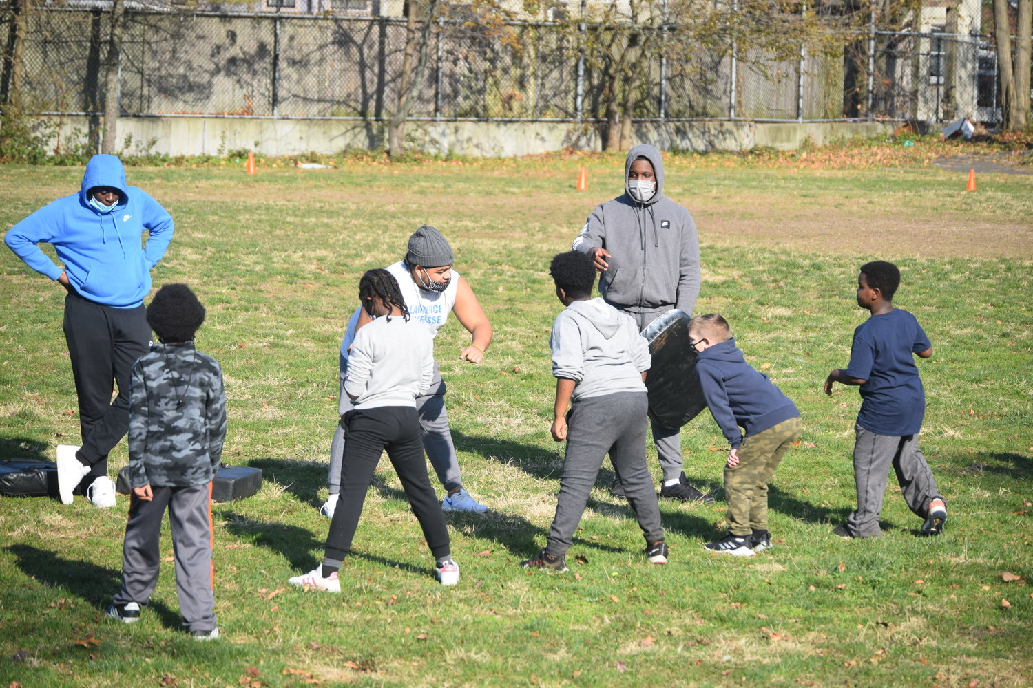 Lawrence High School football player John Calderón, center, taught the children blocking at the football clinic.