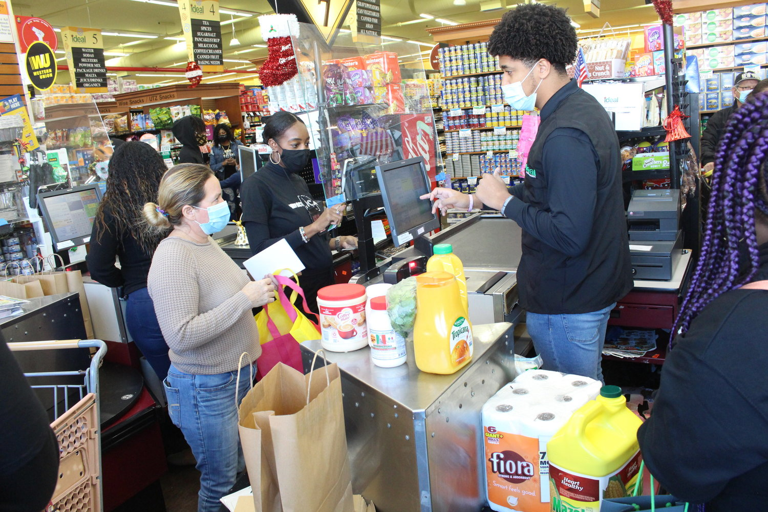 Members of Baldwin's Impact Church helped local families shop for groceries and covered their bills at Ideal Food Basket on Sunday.