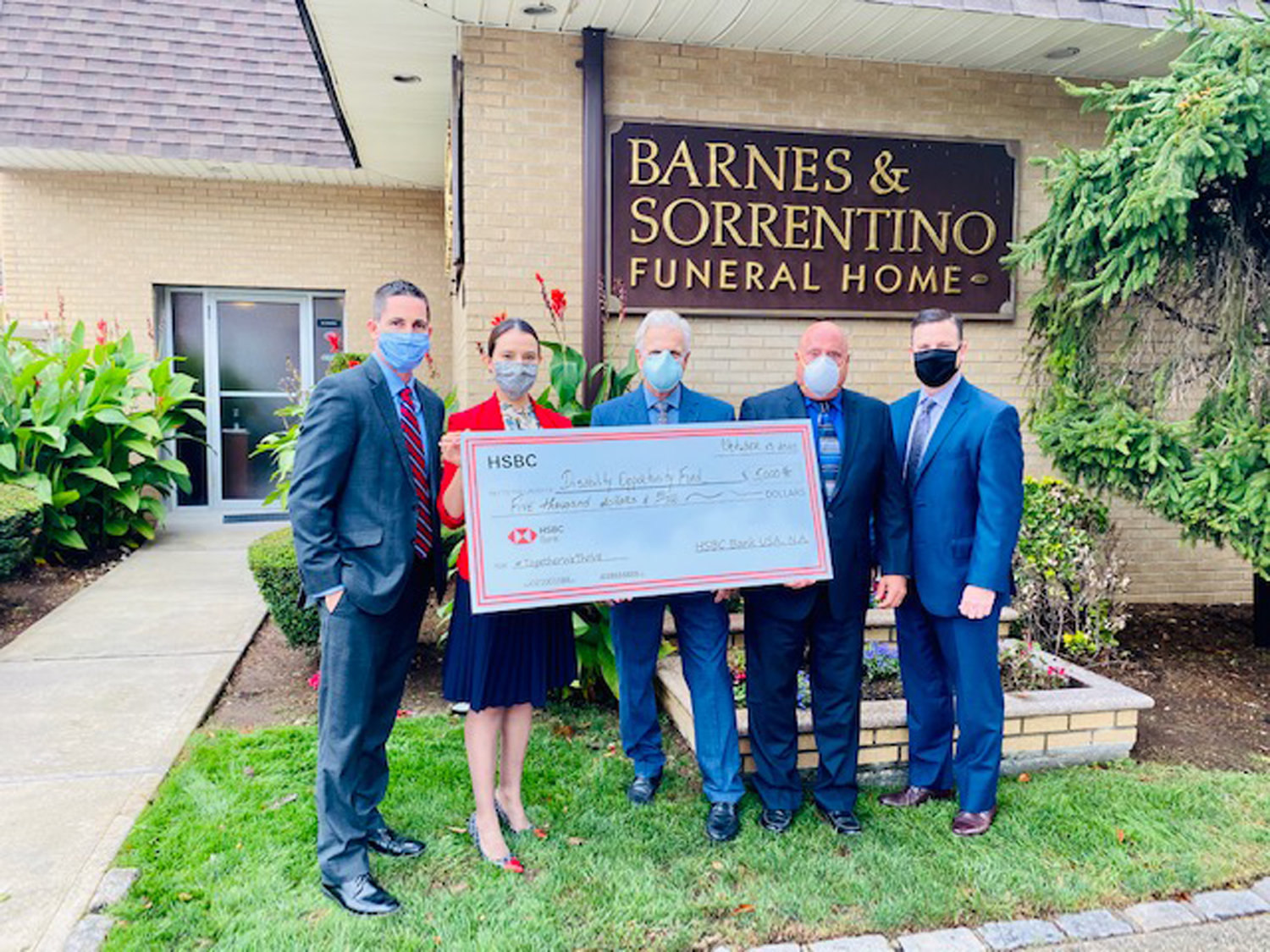 Barnes-Sorrentino Funeral Home owner Frederic Sorrentino, center, and his colleague John Telesca, to his immediate left, received a $5,000 check from HSBC Bank USA, which was donated on their behalf to the Disability Opportunity Fund of Rockville Centre. The two were joined by HSBC area manager Thomas Haggerty, far left, Franklin Square branch manager Zakia Benzoubeier and Senior Vice President Ralph Scannell Jr.