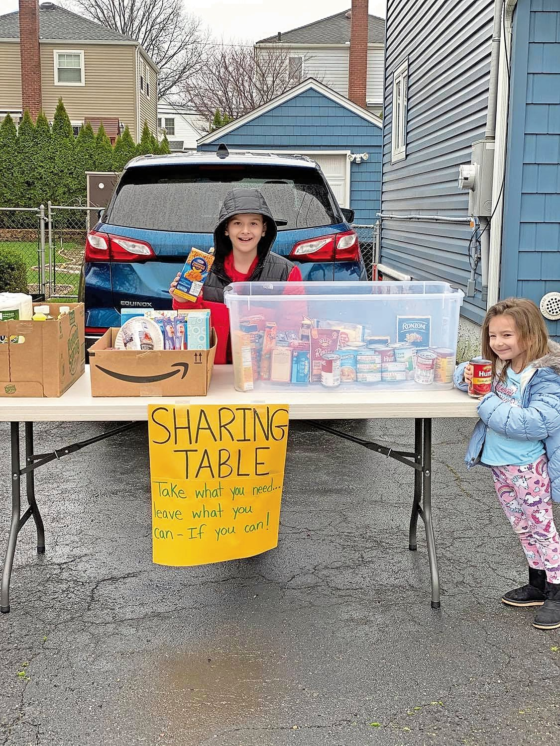 Riley and Hailey Loughlin, 10 and 4, hand out toiletries, cleaning supplies and nonperishable food at their family's Sharing Table on Poppy Street every weekend.