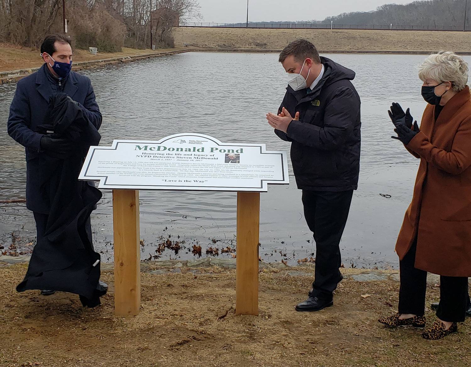 NYPD Sgt. Conor McDonald, center, and his mother, Patti Ann, were the first to see new signage for McDonald Pond, which was unveiled by State Sen. Todd Kaminsky, left, on Jan. 15.