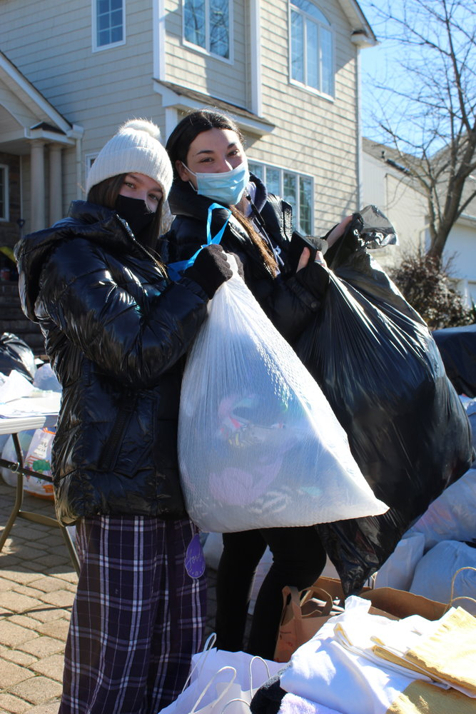 Team members Natalie Schindelheim, front, and Sami Stern, both 16, pitched in to organize the donation pile.