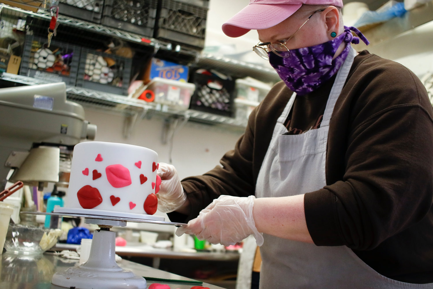 Kristan Newman, the co-owner of Wonderful Wedding Cakes, puts the finishing touches on a cake that was for Valentine's Day as well as a birthday.