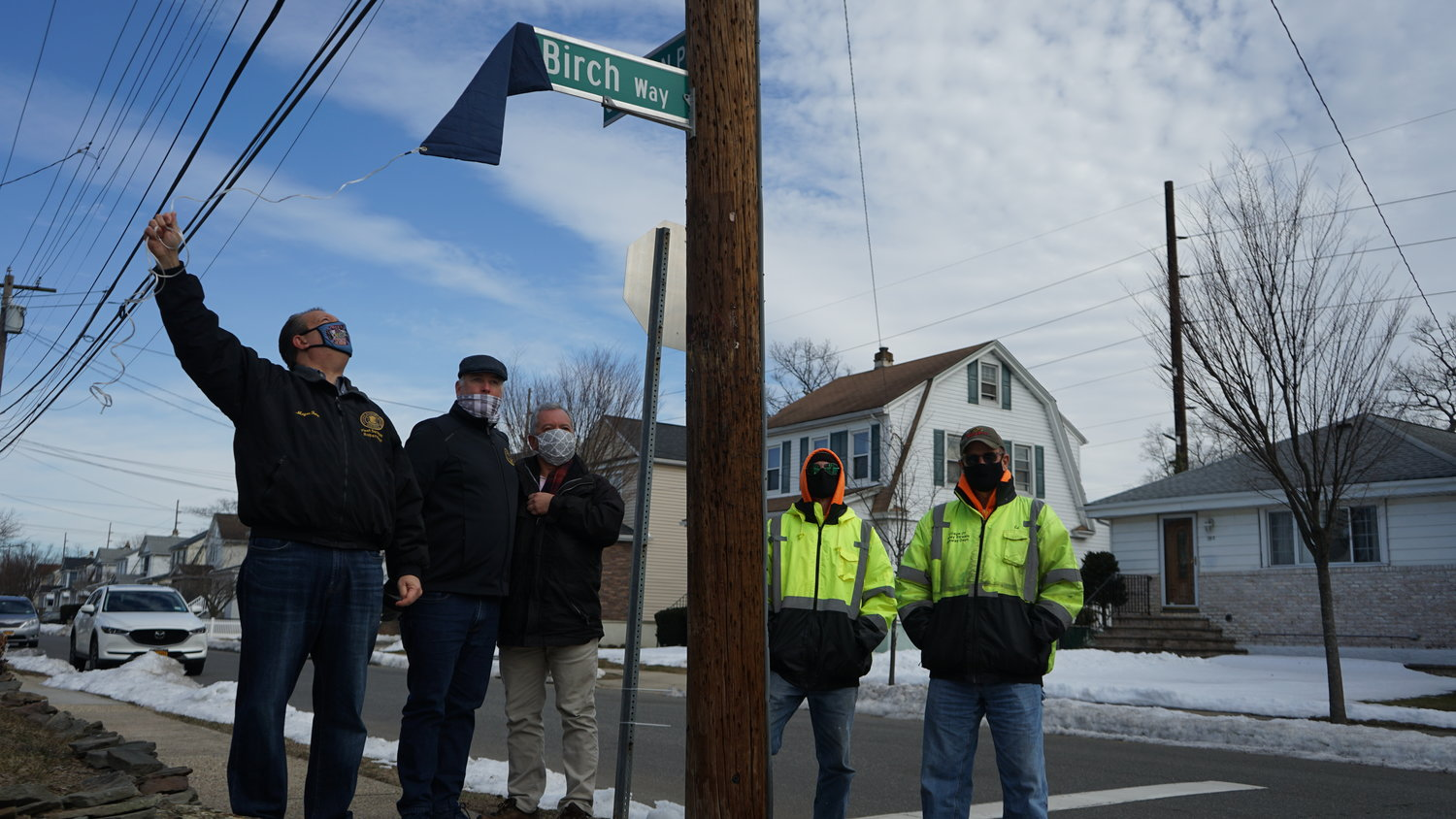 Mayor Ed Fare, from left, Tom McAleer director of community and economic development, neighbor Frank Palacios and village DPW workers unveiled the street sign for the newly renamed Birch Way.