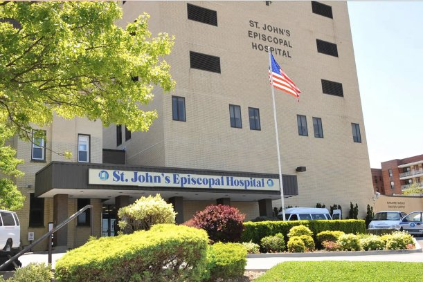 St. John's Episcopal Hospital officials say that the state Department of Health is pressuring them to cut services and staff.