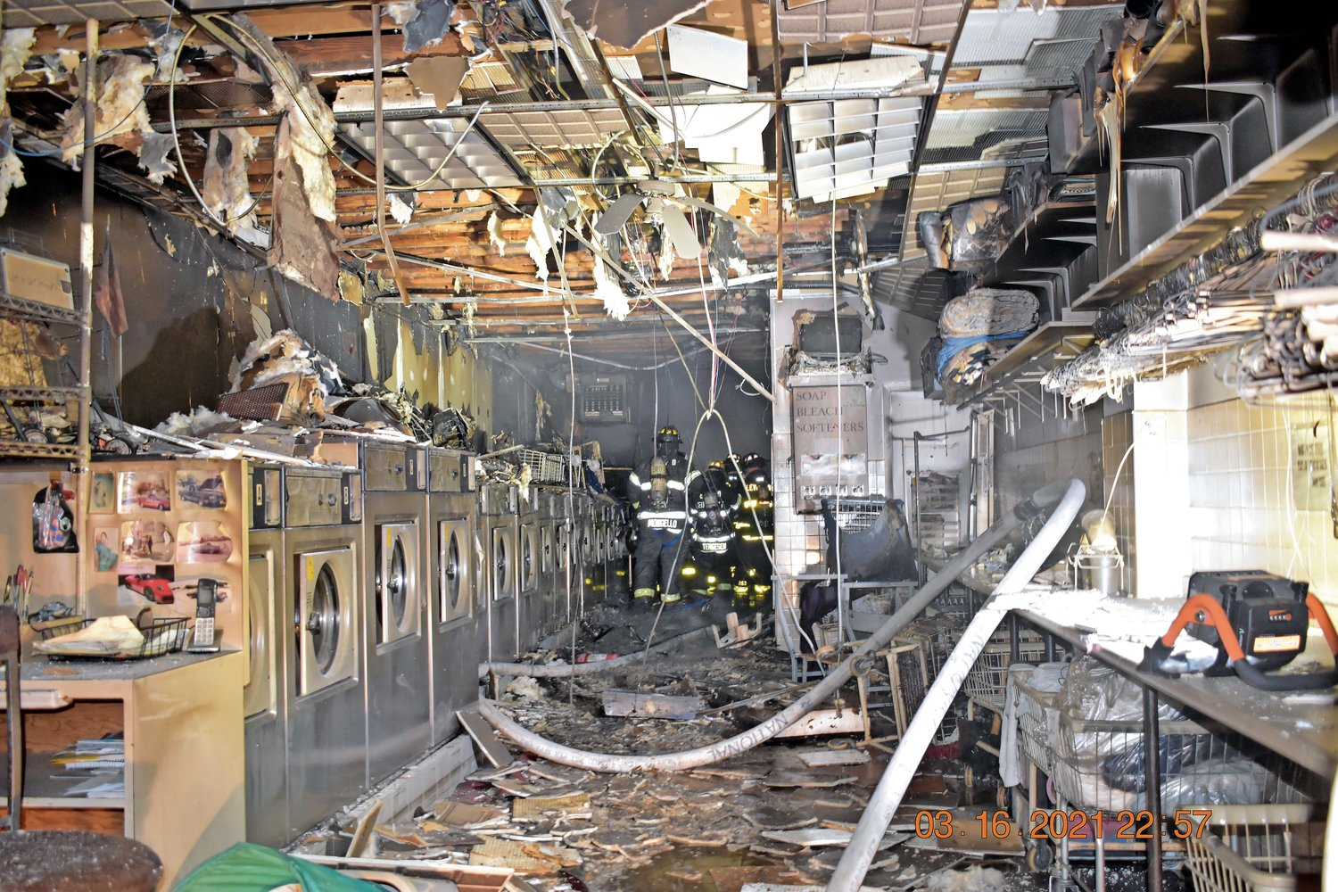 The damage at Every Day Laundromat, left, where the fire began, is extensive.