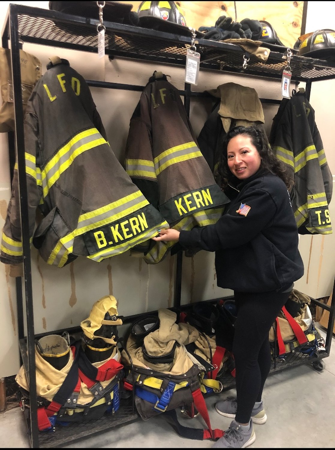 Kern with the coats that she and her husband, Brian Kern, another village firefighter, have hung up at the firehouse.