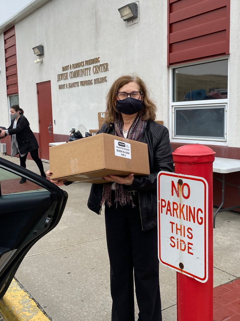 Gloria Lebeaux, the director of social work at the Barry and Florence Freidberg JCC, loaded a Seder box into a delivery volunteer's car as part of the group's Passover donations.