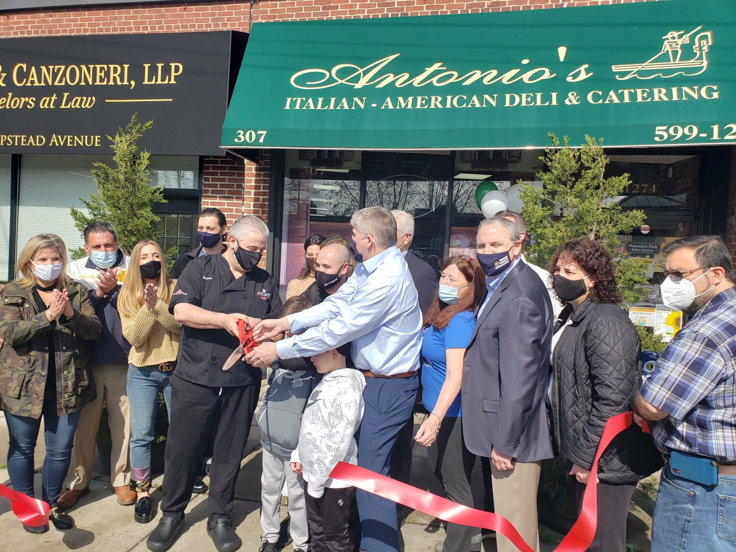 Antonio's Deli owner Antonio Bove, in black at left, and Malverne Mayor Keith Corbett, joined by local elected officials, held a ribbon-cutting ceremony to celebrate the deli's 20th anniversary last Saturday.