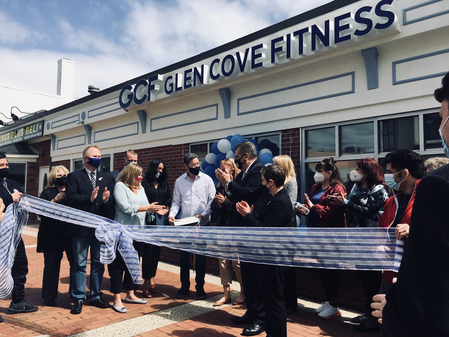 Glen Cove Fitness owner Alvin Batista, center, was congratulated by Mayor Tim Tenke, members of the Chamber of Commerce and the Downtown Business Improvement District for 20 years in business.