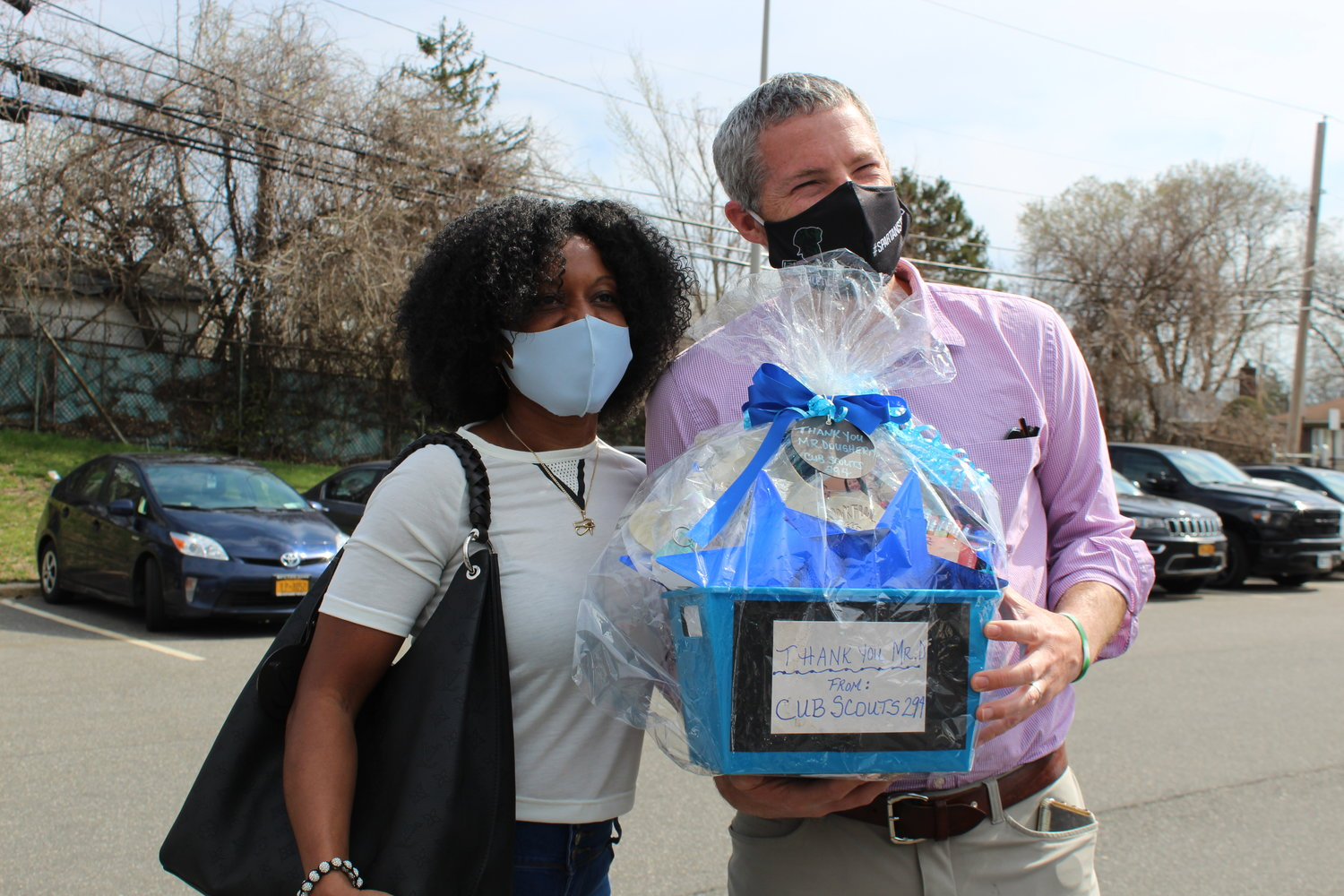 Natasha Warburton presented Elmont Memorial High School Principal Kevin Dougherty with a gift basket on behalf of Cub Scout Pack 294 for his efforts to help feed local families.