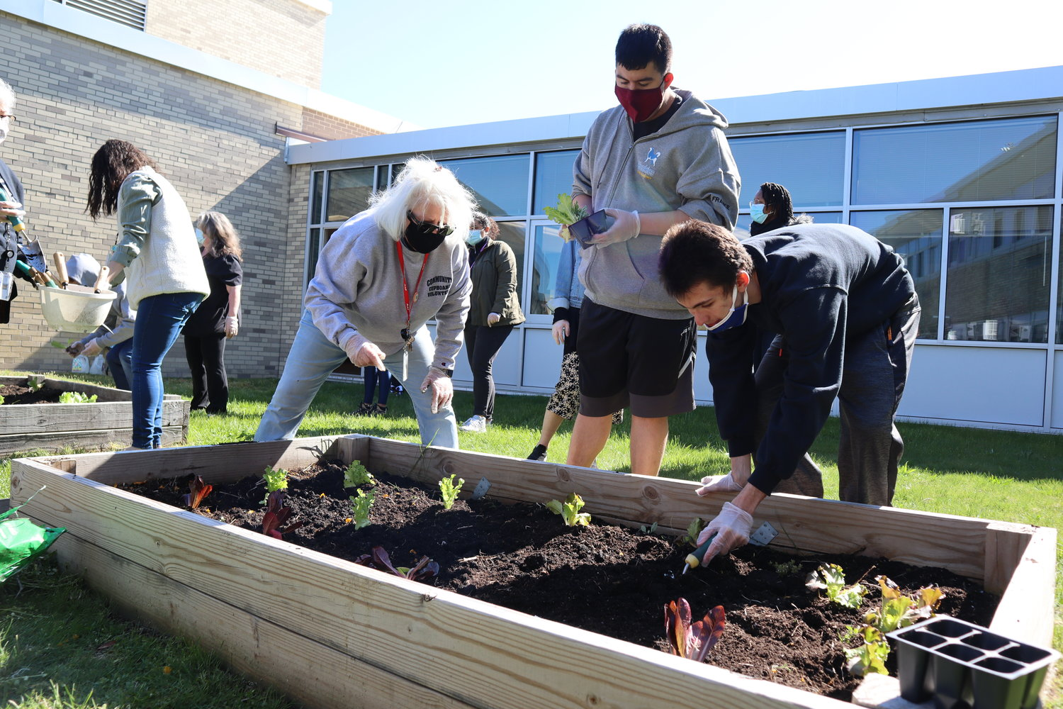 Meadowbrook Alternative Program Principal Susan Ellinghaus, left, helped students James and Jared beautify the Brookside School's courtyard for an Earth Day celebration.
