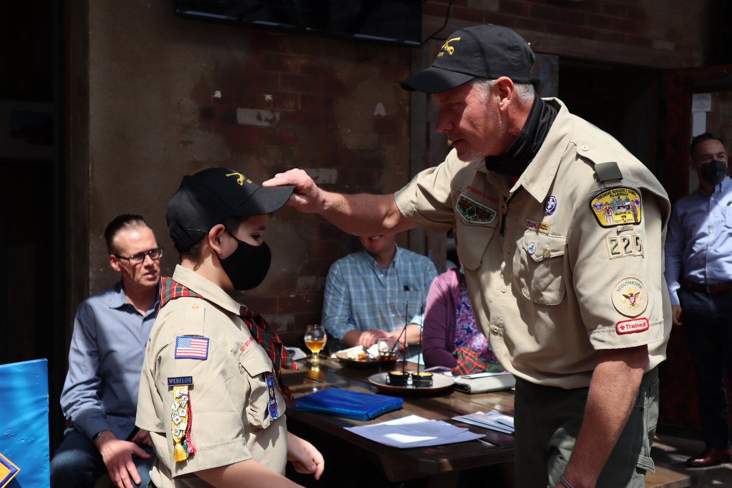 Troop 225 Scout Leader David Walley put a cap on Dezmond Pless, signifying his becoming a Boy Scout and entry into the troop.