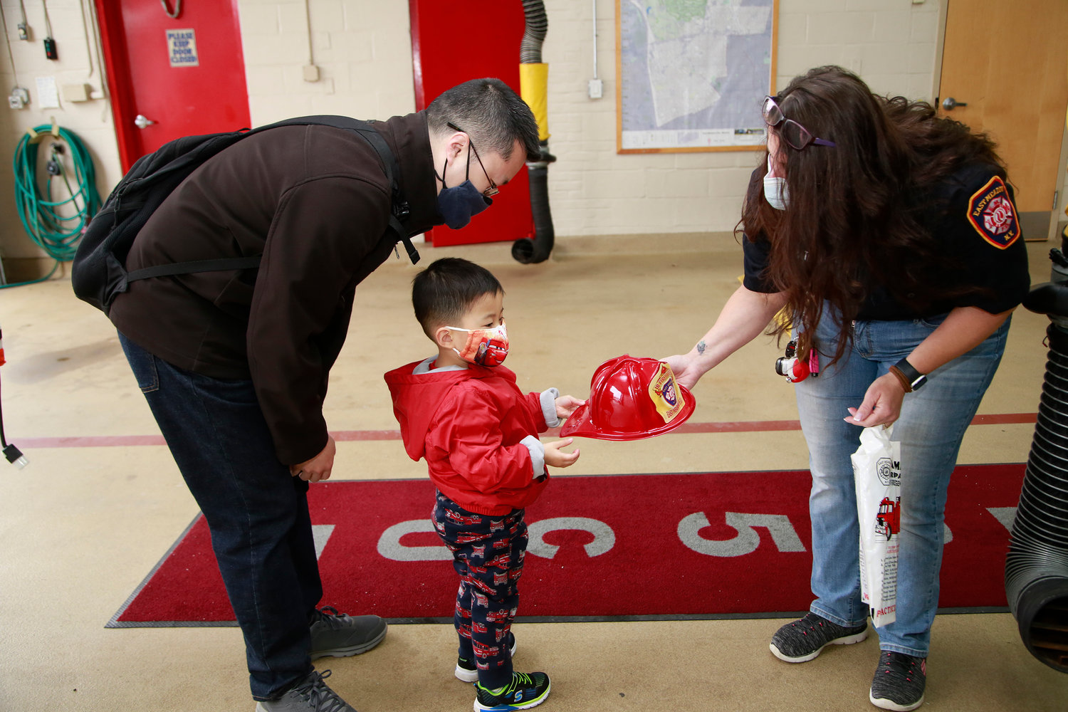 Donald Lim didn't have to coax Theodore, 3, to accept a firefighter's hat from Rescue Co. 5 Capt. Robin Fitzpatrick at RecruitNY last Sunday.