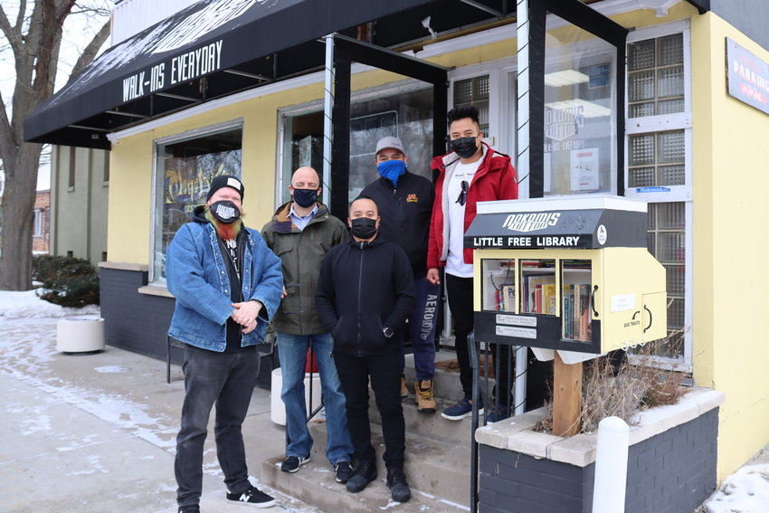 Nokomis Tattoo owner Mike Welch (left) is joined by Ward 11 Council member Jeremy Schroeder, Nokomis Surplus owner Raul Morales, and Grande Sunrise Restaurant owners Javier (front) and Roberto Grande to launch the bilingual Little Free Library on Jan. 20, 2021. (Photo by Tesha M. Christensen)