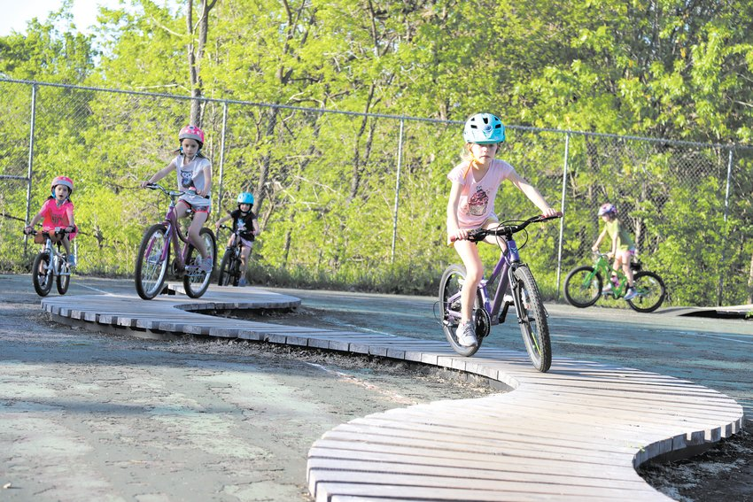 Zaylee Olson (7) leads a group of girls on the snake at the Nokomis Bike Skills Park, the first of its kind in the city. Supporters hope more like it are built.  (Photo by Tesha M. Christensen)