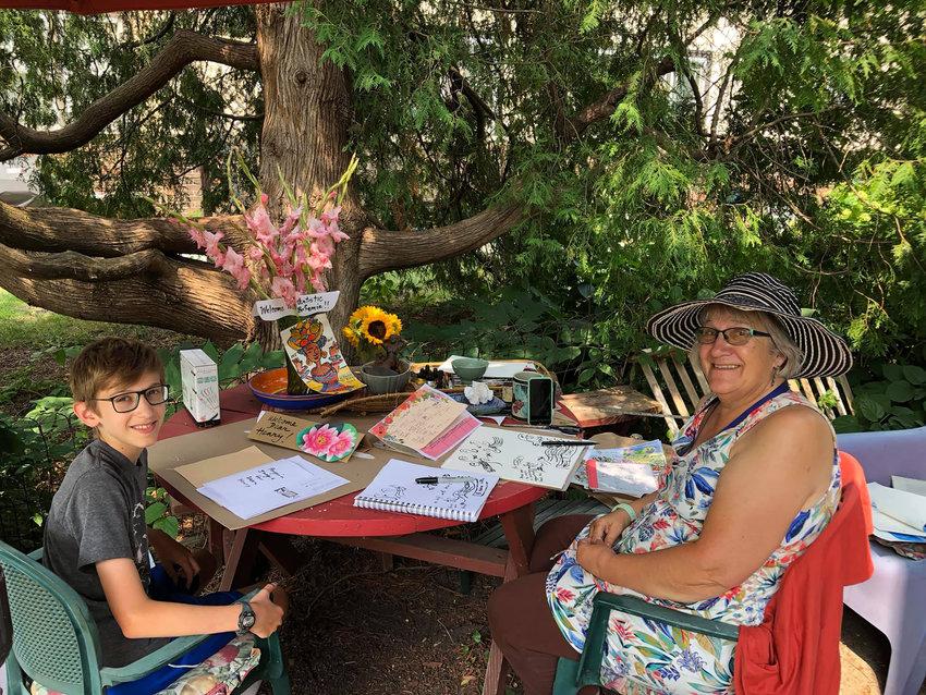 Artist Anita White (right) with art student Henry Holdsworth, in White's garden. (Photo courtesy Hillary Oppmann)