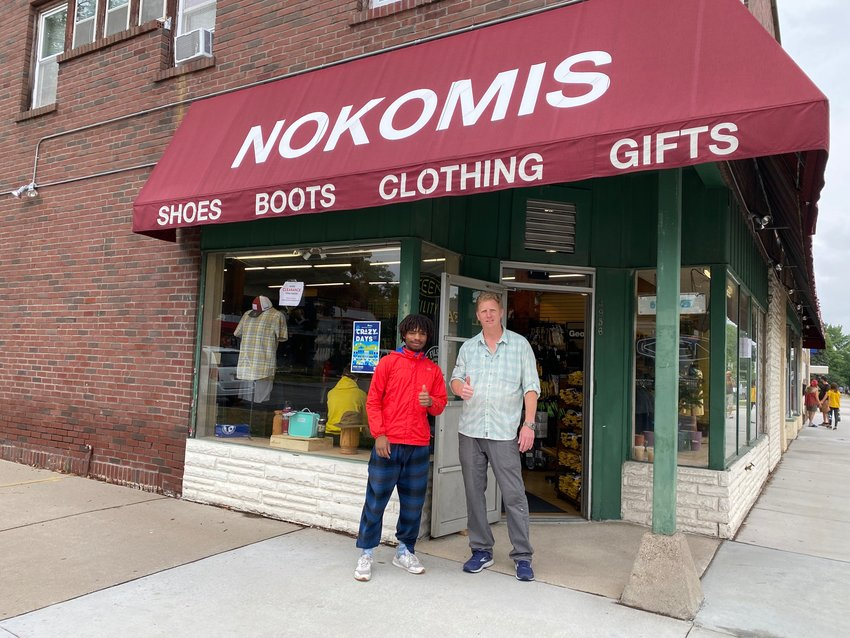 """Nokomis Shoe Shop owner Steve Negaard (right) with Tre McClellan welcome folks into the store for the sidewalk sale, which moved instead after it rained on Saturday, Aug. 7. Negaard was delighted to see other business engaging in Crazy Days again. """"As a guy who has been doing it for 45 years, it's so fun to see the neighborhood coming back alive,"""" he said. Nokomis Shoes used to be located next to the bowling alley (formerly Skylanes, now Town Hall) and items filled the sidewalk in front of the bowling alley. """"I remember being a kid in high school and dreading working the long days in the heat,"""" said Negaard."""