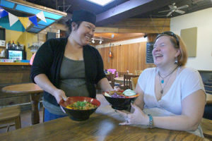 "first-time customer, Mrs. Reyn Martin shares a laugh with Mai Vang. ""The food is great,"" she said."