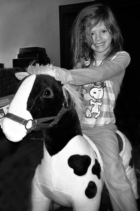 Erin Pavlica's daughter in 2013, riding the used upholstered horse that became the inspiration for the Midway-Frogtown Exchange. The group offers a place for Midway and Frogtown neighbors to buy, share and barter. (Photo submitted)