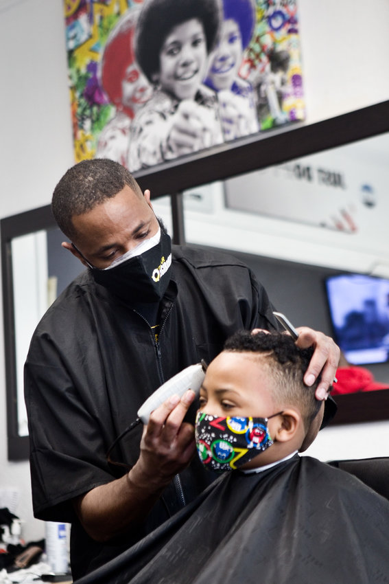 "Milan Dennie, owner of King Milan's Barbershop said, ""We're a standout small business in the neighborhood because we stand for something positive."" (Photo by Margie O'Loughlin)"