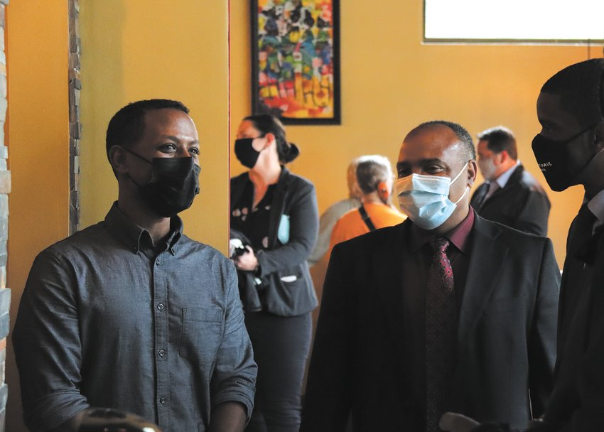 """olomon Hailie (left), who owns Bole Ethiopian with his wife, Rekik Abaineh, chats with African Economic Development Solutions Executive Director Gene Gelgule (center) and St. Paul Mayor Melvin Carter during the ribbon cutting event on May 27, 2021, one year after the restaurant burned to the ground in the civil unrest along University Ave. after George Floyd's murder.    """"When we needed something, we knew who to call,"""" stated Hailie. """"We appreciate your support and love."""" They received a $50,000 grant through the We Love St. Paul/We Love Midway fund to help with the new space in the former Fox Trot Burger (1341 Pascal Street). """"Thank you for leading the way,"""" said Midway Area Chamber of Commerce Executive Director Chad Kulas. (Photos by Tesha M. Christensen)"""