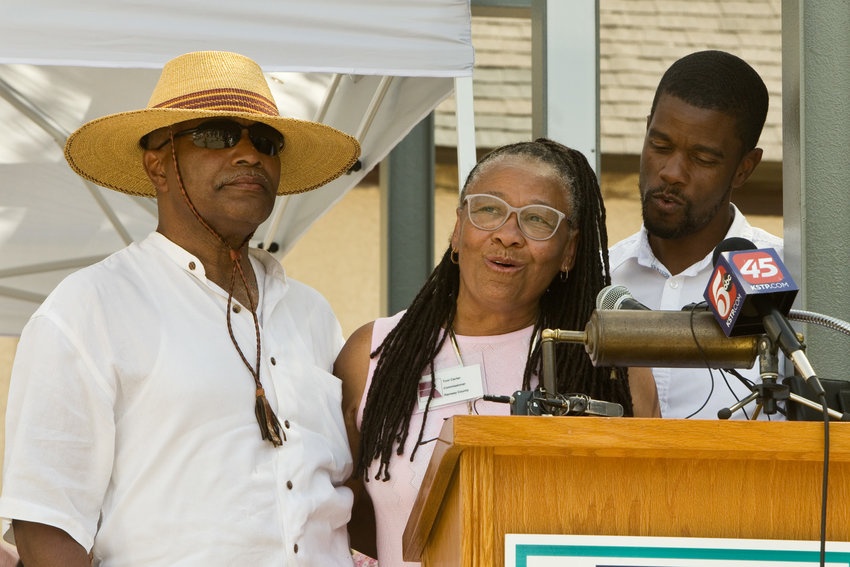 Ramsey County Commissioner Toni Carter (center), husband Melvin Carter Junior (left) and son St. Paul mayor Melvin Carter III (right) commemorated their family's original Rondo home that was uprooted during the construction of I-94 by planting a tree during the Juneteenth Celebration at the Rondo Center of Diverse Expression at 315 Fisk St. (Photo by Margie O'Loughlin)