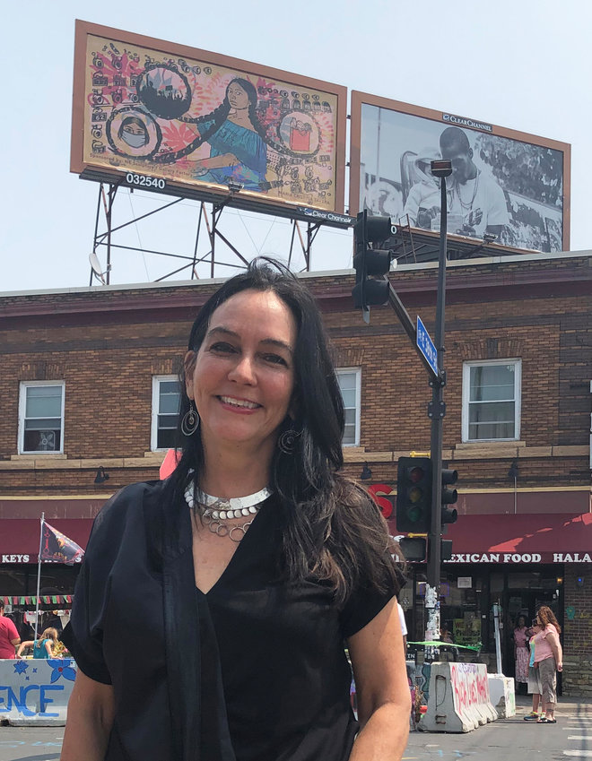 """Tina Tavera stands with her billboard """"La Conneccion"""" on the Cup Foods rooftop behind her. (Photo by Jill Boogren)"""