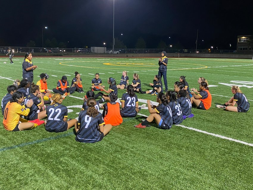 The Cougar girls soccer team gathered on the Como turf after their opening match of the season (Photo by Eric Erickson)