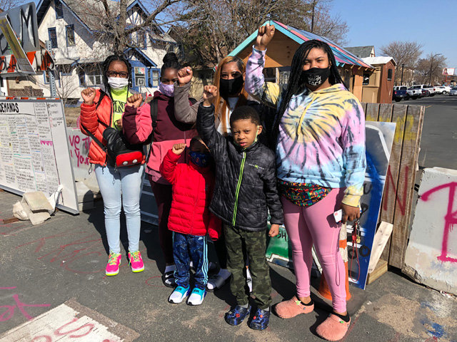 "Left to right: Simya Edwards, Milaen Mullins, Schiantae Mullins, Malachi Mullins, Levi W., NaJee W., from the Metro area of Detroit, Michigan, visit George Floyd Square. ""It gives me goose bumps bein' here,"" said Mullins."