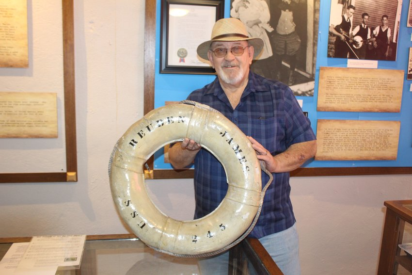 Michael Sinks, Director of the Woody Guthrie Folk Music Center, with the life raft from the   USS Reuben James, the first ship sank in the European Theater of World War II.