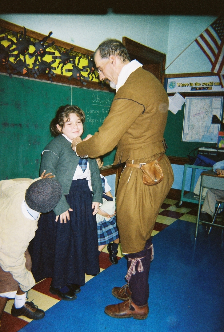 "Pilgrim Jonathan Brewster helps Alexandra Azero (a third grade student at Blessed Sacrament School) don the clothing of a Pilgrim girl.  Each year third graders at Blessed Sacrament School study the Pilgrims as part of their social studies unit.  Jonathan Brewster (an interpreter from Plimoth Plantation) presented a workshop for students on ""Life in Plimoth Colony"" on October 29th. 
