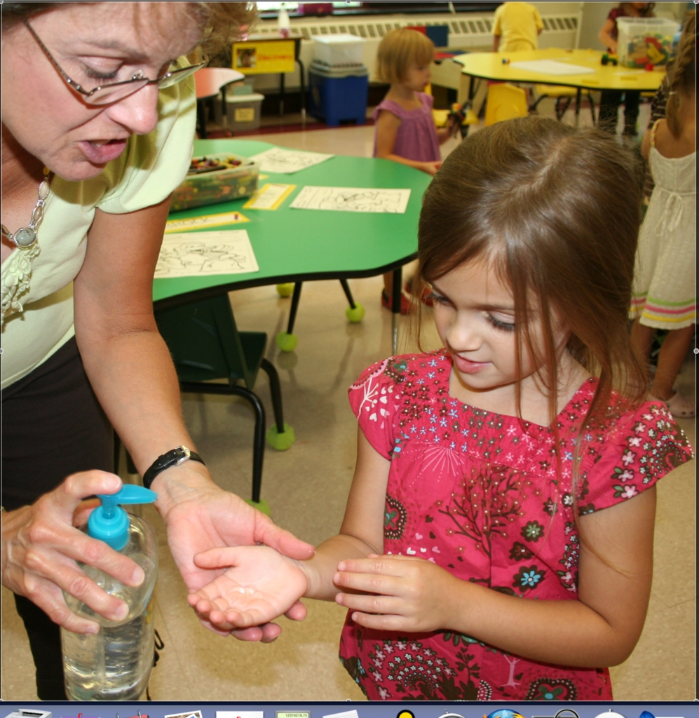 PREVENTION:  Claire Forand, Our Lady of Mount Carmel School's pre-kindergarten teacher, helps Teah Mason apply hand sanitizer.