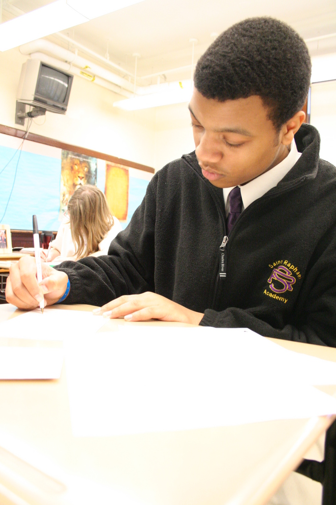 "APPRECIATION: Damien Ferreira, 16, of Warwick writes a thank you note to the generous people who have helped him to attend Saint Raphael Academy. Students spent their religion classes writing ""thank you"" valentines to those who made their Catholic education a possibility."