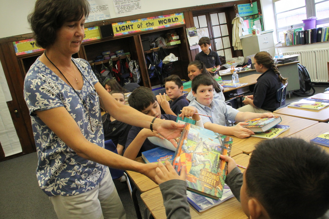 BUY THE BOOK: St. Pius teacher Sharon Dragon hands out textbooks to her sixth grade class. Under a budget cut proposed by Rhode Island's education commissioner, state money to support the textbook loan program for the parents of private and parochial school students would be eliminated.