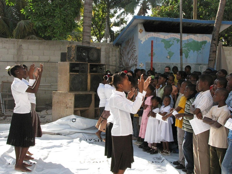 PRAYER IN MOTION: Older students lead the younger ones in prayer at The Haitian Project's Louverture Cleary School in a photo taken by Gerry Grabowski, a member of St. Bernard Parish, North Kingstown, who in April volunteered her services as a nurse during a mission trip.