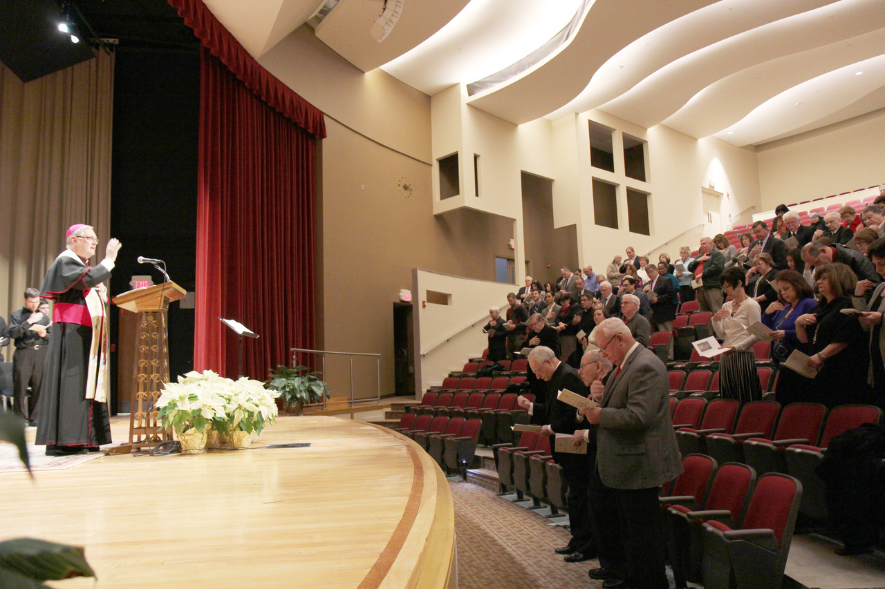 TAKING THE STAGE: Bishop Thomas J. Tobin blesses the rededicated Bishop McVinney Auditorium on Thursday, Jan. 15. The newly renovated facility will be available for church and community functions. In attendance in the first row, at right, is Thomas Blessington, nephew of Bishop McVinney.