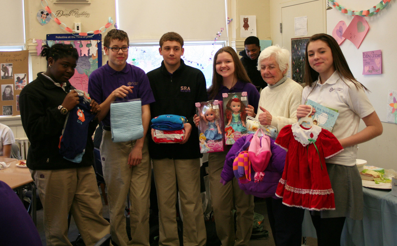 "From left to right, Oluwatoyin ""Toyin"" Okele, Nick Huntley, Bryce Gillis, Sara Langlois, Mrs. Joan Crowley from Holy Family Church, and Ruby Costello display some of the shower gifts."