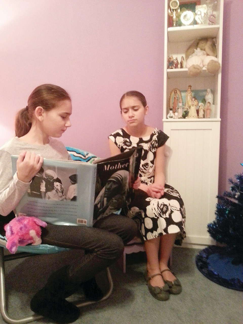 Sydney Khoury, now 13 and a seventh-grader at St. Philip School, reads one of her story books on the life of Mother Theresa with her younger sister Ava, 12, a student at St. Thomas.