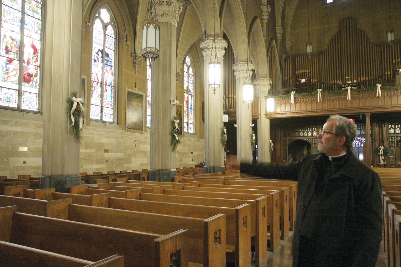 Preserving history: Msgr. Jacques Plante, pastor of the Church of St. Mary, points to the restoration work planned for the Providence church's stained glass windows thanks to a $50,000 grant it has been awarded.